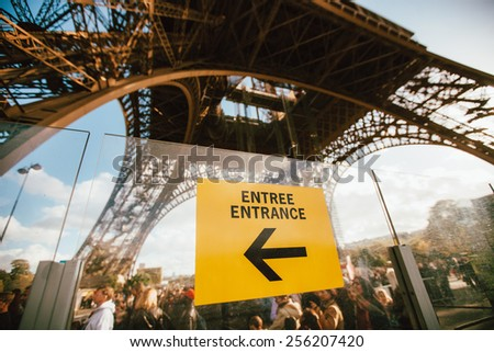Arrow which shows direction to the entrance of Eiffel tower, Paris France - stock photo