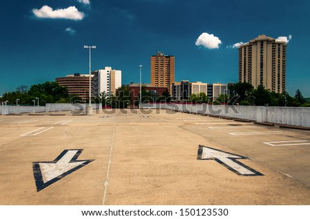 Arrows in parking lot and view of highrises from a parking garage in Towson, Maryland. - stock photo
