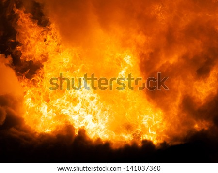 Arson or nature disaster - burning fire flame on wooden house roof - stock photo