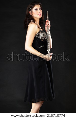 Art and artist. Portrait of woman girl flutist flautist performer with flute musical instrument on black. Classical music. - stock photo