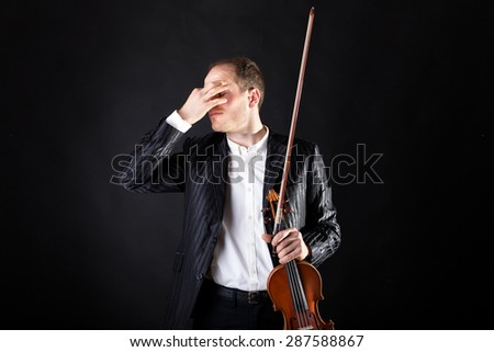 Art and artist. Young elegant man violinist fiddler with his violin lookfor concentration before concert. isolated studio portrait on black background. Classical music.waiting for the show.