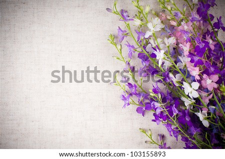 Art background with bright purple wild flowers on linen fabric