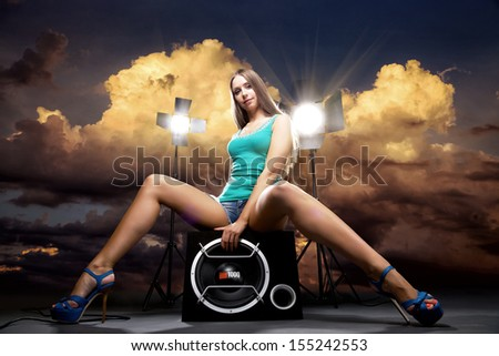 Art Beauty Portrait of Beautiful Girl seating on loudspeaker with sunset background