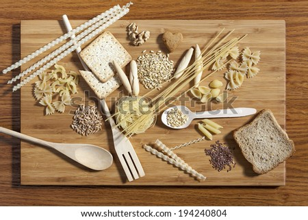 Art composition of pasta, grains,  whole grain bread, wooden kitchen set placed on wooden cutting board and wooden background - stock photo