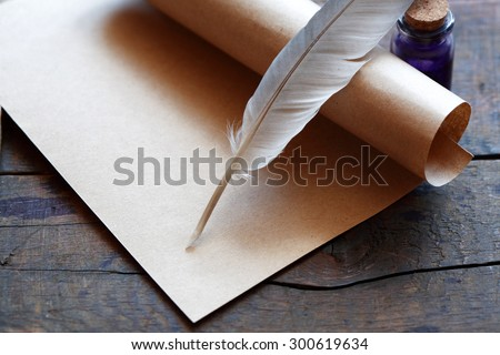 Art concept. Closeup of scroll and quill near ink-pot on wooden table - stock photo
