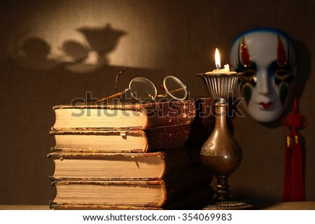 Art concept. Vintage still life with old books near lighting candle
