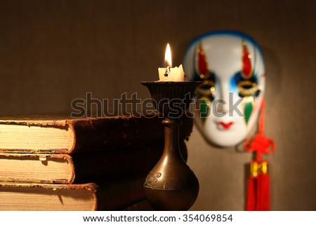 Art concept. Vintage still life with old books near lighting candle against venetian mask - stock photo