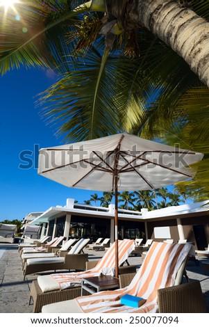 art Deckchairs in tropical resort hotel pool - stock photo