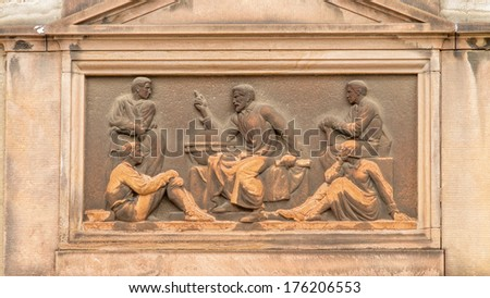 Art Deco inspired classical relief of a teacher or story teller sitting next to a globe surrounded with pupils