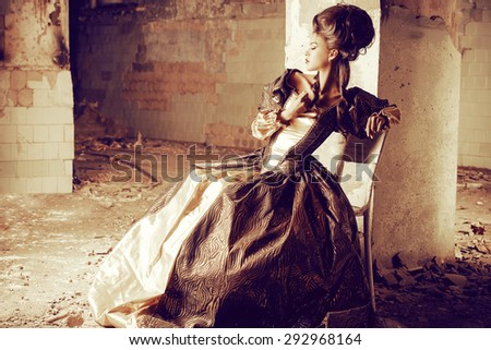 Art Fashion. Beautiful young woman in elegant historical dress and with barocco updo hairstyle posing in the ruins of the castle. Renaissance. Barocco. - stock photo