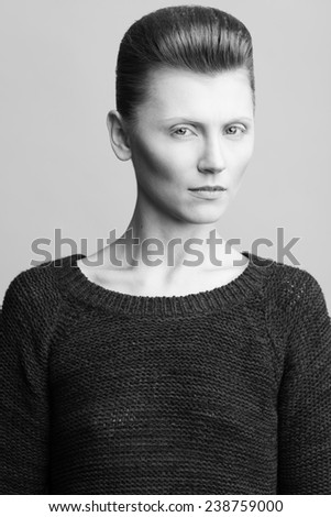 Art fashion concept. Portrait of androgynous model with short hair in knitted sweater posing over gray background. Pale skin, serious face, natural make-up. Close up. David Bowie style. Studio shot - stock photo