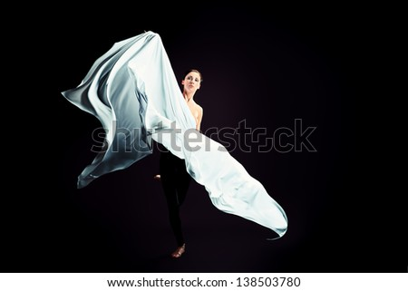 Art fashion photo of a beautiful woman dancing over black background.