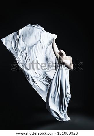 Art fashion photo of a beautiful woman dancing over black background. - stock photo