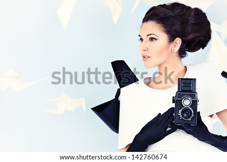 Art fashion photo of a gorgeous woman in paper dress holding old camera. Black and white. - stock photo