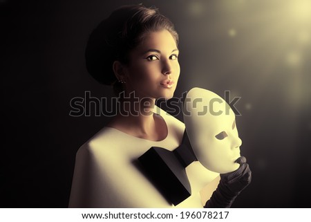 Art fashion photo of a gorgeous woman in paper dress holding theatrical mask. Black and white.