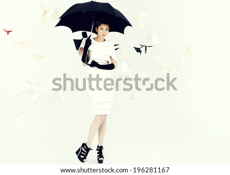 Art fashion photo of a gorgeous woman in paper dress holding umbrella. Black and white.