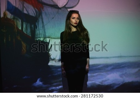 Art fashion portrait of young stylish girl in black clothes with painting on a screen - stock photo