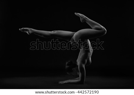 Art nude. Perfect flexible sexy body of young woman on black background. Vrischikasana or scorpion pose. Studio shot - stock photo