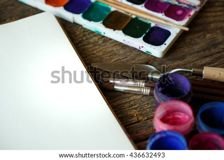 Art of Painting. Painting set: paper, brushes, paints, watercolor, acrylic paint on a wooden background top down view