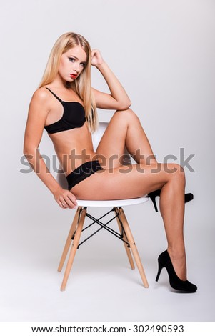 Art of seduction. Side view of young woman in black bra and panties posing while sitting on the chair against white background