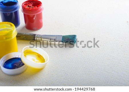 Art paint brush lying on a cardboard with gouache paints - stock photo
