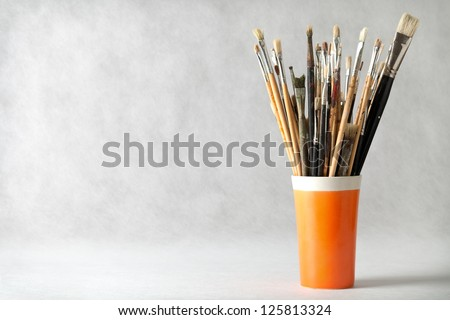 Art paint brushes in cup with empty room for text - stock photo
