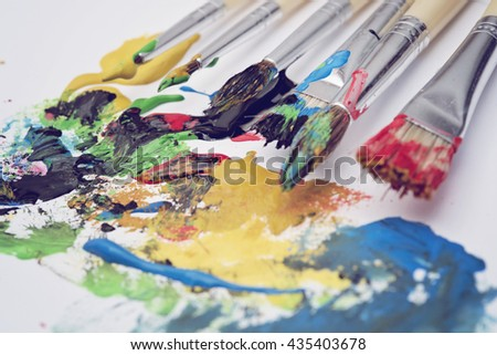 Art painting brushes and colorful paste on white canvas