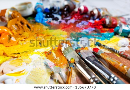 Art palette with oil paints and brushes. theme with paint brushes and palette - stock photo