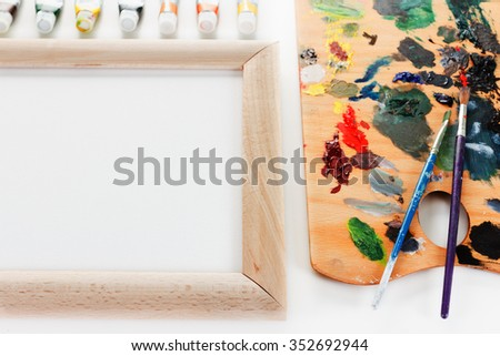 Art palette with paint, border and a brush on white background - stock photo