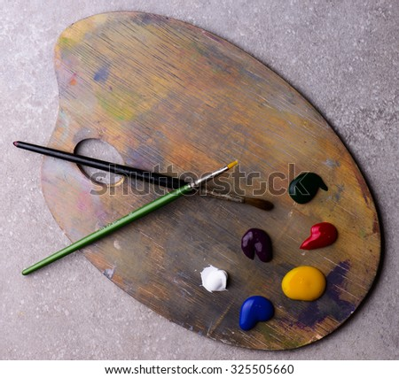 art palette with two brushes and colors - stock photo