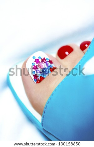 Art pedicure with crystals on women's legs with rhinestone sandals blue on a white background. - stock photo