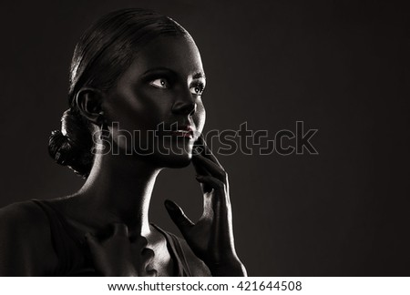art photo of a woman painted with black color, over black background, portrait in low key - stock photo