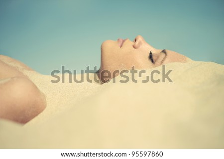 Art photo of beautiful lady buried in the sand - stock photo