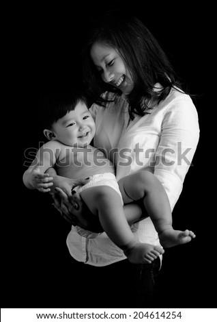 Art photo of beautiful mother holding baby boy smiling. Black and white image - stock photo