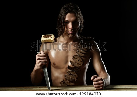 Art photo of young man with beard of bread isolated over black background - stock photo