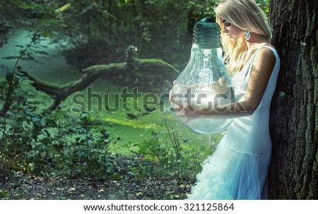 Art photo - stunning blonde beauty holding a big lightbulb - stock photo
