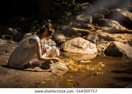 Art portrait a beautiful girl,in nature forest light,fashion style of young pretty beautiful woman and horse doll in stream