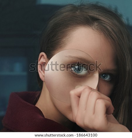 Art portrait of a beautiful girl with a lens in hand - stock photo
