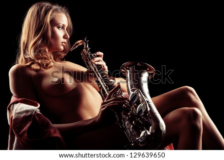 Art portrait of a beautiful naked woman with saxophone. - stock photo