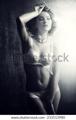 Art portrait of a beautiful slender young woman alluring in sexual lingerie. Black-and-white photo. - stock photo