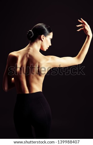 Art portrait of a beautiful  woman back over black background.