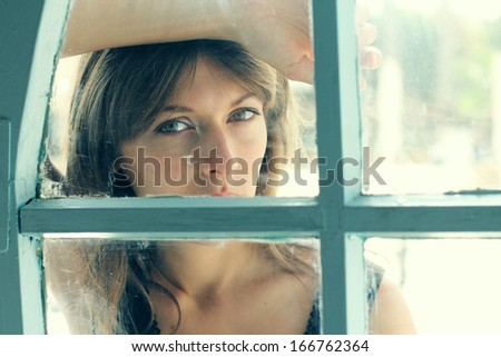 Art portrait of a beautiful young sadly girl looking through the window