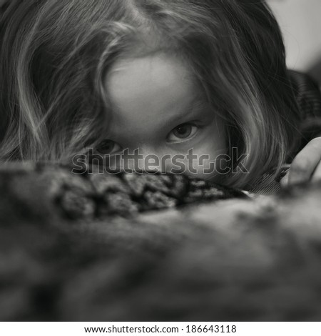 Art portrait of a child's play, a little girl playing hide and seek - stock photo