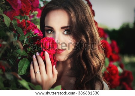 Art portrait of a girl brunette on a background of roses