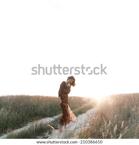Art portrait of a lonely girl in a transparent dress in the wind in the field - stock photo