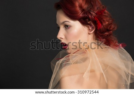 Art portrait of a redheaded girl with transparent fabric - tulle