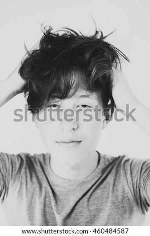 Art portrait of a teenager that is messing up his hair.