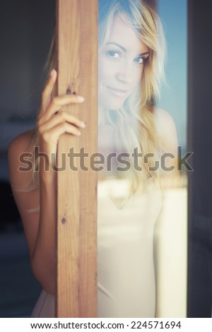 Art portrait of beautiful blonde through the glass