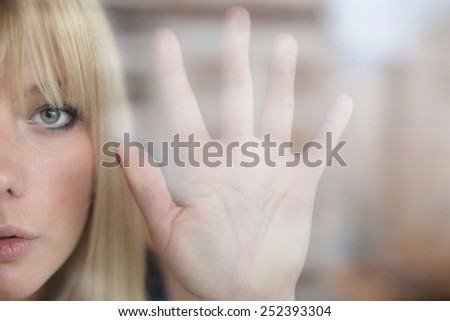 Art portrait of beautiful blonde through the glass - stock photo