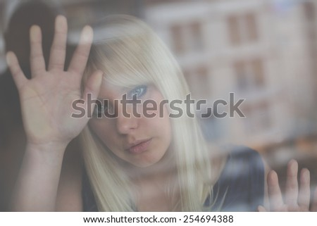 Art portrait of beautiful blonde through the glass - stock photo